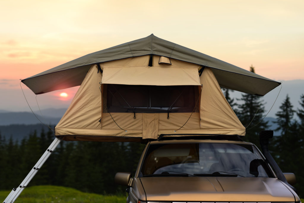 Car camping tent on the rooftop of an SUV in mountains